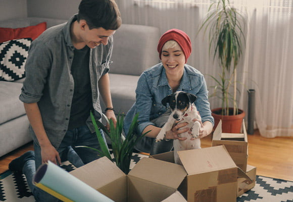 Small squared image of a couple unboxing as they move into their new home, with woman holding dog