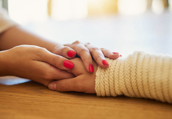 Two hands of one person holding another persons hand.