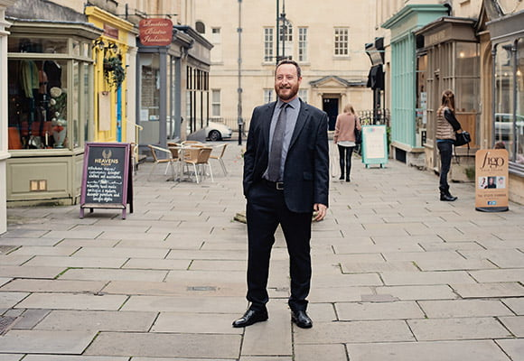 Image of a man stood in the centre of a commercial property avenue wearing a suit.