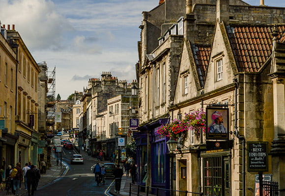 Image from the bottom of a city centre street in Bath, looking uphill. Pubs, shops and other commercial properties line the street with cards and people heading up and down the street.