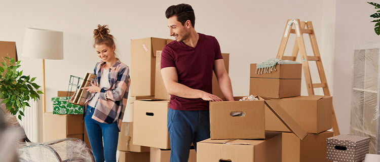 Image of man and woman unboxing in their new home, ladder and lamp in background and other items wrapped up.