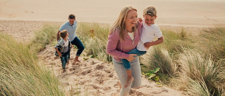 Landscape image of couple and two sons family at the beach climbing sand dune