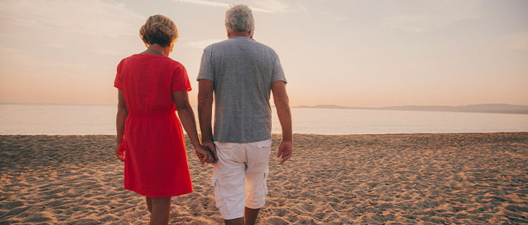 Retired couple hold hands as they walk along the beach towards the sun and sea.